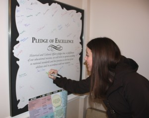 Historic-site interpreter Melissa Fitzgerald signing the Pledge of Excellence.