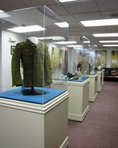 "Display cases at the ""Middletown Goes to War"" exhibit. In the foreground is a German field-blouse from World War II."