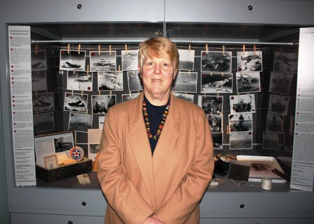 "Carolyn Apple in front of the display, ""World War II Through the Lens of William D. Willis."""