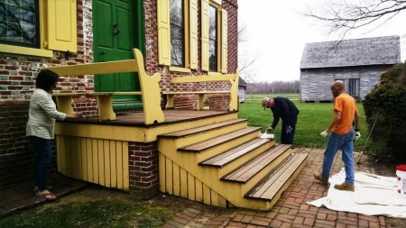 Volunteers staining the entrance stairs to the John Dickinson Plantation's mansion house during a National Volunteer Week project in 2015.