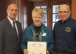 Carolyn Apple accepting the Extra Mile Award. (Form left) Delaware Secretary of State Jeffrey W. Bullock, Apple and Tim Slavin, director of the Delaware Division of Historical and Cultural Affairs. Photo by Howard Fulcher.