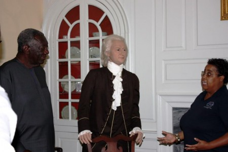 President Kufuor (left) listens to Gloria Henry (right). At center is a museum figure depicting John Dickinson.
