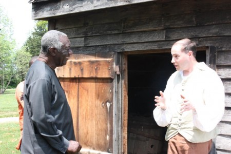 President Kufuor listens to historic-site interpreter Chris Merrill outside the plantation's smokehouse.
