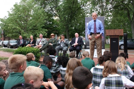 Sen. Tom Carper speaking at the interpretive-sign unveiling ceremony. In the foreground are first-grade students from Holy Cross School. Seated in the rear are (from left) Delaware Secretary of State Jeffrey Bullock, Delaware Department of Transportation Secretary Jennifer Cohan, state Sen. Brian Bushweller, First State National Historical Park Superintendent Ethan McKinley, Dover Mayor Robin Christiansen and Tim Slavin, director of the Delaware Division of Historical and Cultural Affairs.