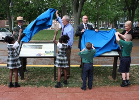 First-grade students from Holy Cross School assist in the unveiling of interpretive signs on the Dover Green. In the background, from left are First State National Historical Park Superintendent Ethan McKinley, Sen. Tom Carper, Delaware Secretary of State Jeffrey Bullock and Delaware Department of Transportation Secretary Jennifer Cohan.
