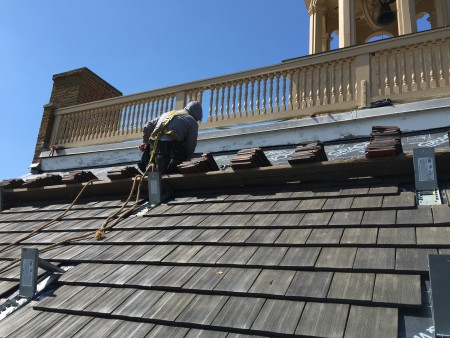 Worker installing shingles on the New Castle Court House roof in April 2015.