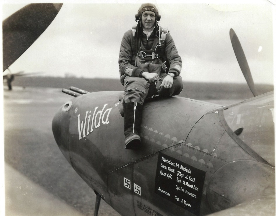 Mission symbols on a P-38 Lightning fighter aircraft. Capt. Merle B. Nichols of the 79th Fighter Squadron, 20th Fighter Group, 8th Air Force, sitting atop Wilda.