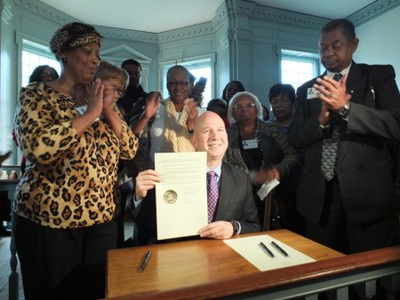 Surrounded by Burris-family descendants, Gov. Jack Markell holds the document pardoning Samuel D. Burris. In the foreground at the far left is Ocea Thomas. At far right is the Rev. Ralph D. Smith, Sr.