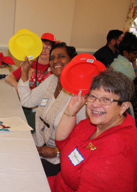 Division of Historical and Cultural Affairs historian Madeline Dunn (foreground) and New Castle County's Josie Roy tip their hats to the division's staff, volunteers, partners and friends at the Dec. 14, 2015 event. Administrative specialist Jan Rettig (rear) looks on.