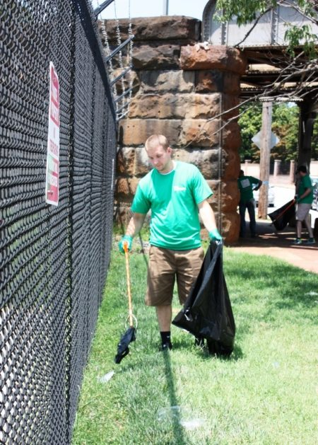 Volunteer helping to clean areas along East Seventh Street on July 19, 2016.