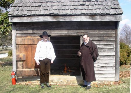 Historic-site interpreters in front of the John Dickinson Plantation smokehouse.