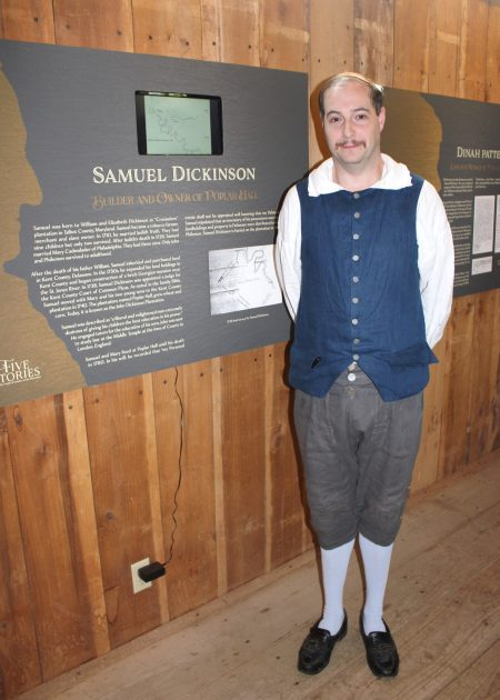 "Historic-site interpreter Chris Merrill standing in front of a section of ""Five Stories."""