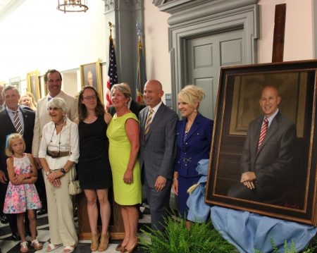 Unveiling ceremony of former Gov. Jack Markell's portrait at Legislative Hall. (From rear left) Gov. John Carney and David Larned. (From left foreground) Sadie Larned, Elaine Markell, Molly Markell, former Delaware first lady Carla Markell, former Gov. Markell and Lt. Gov. Bethany Hall-Long