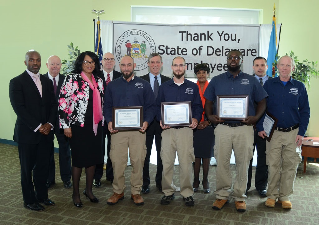 Division of Historical and Cultural Affairs employees Greg Buchman, Scott Hayes and James Scott (center in blue shirts holding their certificates) who were honored with a Delaware Award for Heroism. Pictured from left: Kristopher Knight, Delaware deputy secretary of state; Justice James T. Vaughn, Jr. of the Delaware Supreme Court; Deloris Hayes-Arrington, director of human resources for the Department of Finance; Tim Slavin, director of the Division of Historical and Cultural Affairs; Buchman; Gov. John Carney; Hayes; state Rep. Stephanie T. Bolden; Scott; Michael S. Jackson, secretary of the Office of Management and Budget; and Division of Historical and Cultural Affairs' physical-plant maintenance supervisor Ed Gillespie. Not pictured: Chris Conley.