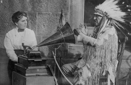 Mountain Chief (Ninastoko), chief of the Blackfeet Tribe, listening to a song on a phonograph and interpreting it in sign language to the ethnologist Frances Densmore in Washington, D.C. in 1916.