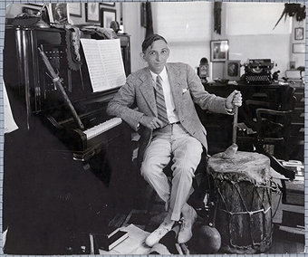 Charles Wakefield Cadman posing in his studio with several Native-American musical instruments.