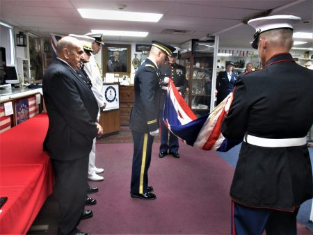 1st Lt. Christopher Watkins presides over the ceremonial folding of the HMS Sheffield flag by two U.S. Marines. Standing from the left are former Newark Police Chief Bill Brierley, Maj. Justin Bellman and Cmdr. Richard McHugh.