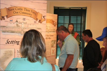 "Opening day visitors examining a display panel from the exhibit ""New Castle: Three Forts, One Community."""