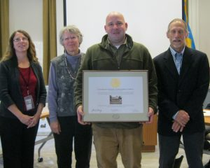 Cox-Phillips-Mitchell Agricultural Complex owner Peter Seely holding his National Register certificate. (From left) Gwen Davis; Peter's mother Barbara Seely; Peter Seely; and John Martin
