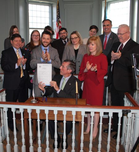 Gov. John Carney holds up a copy of the Abandoned Cultural Property Act which he had just signed into law. Looking on from the back row left are University of Delaware Museum Studies students Kathryn Lenart, Sara McNamara and Tess Frydman (obscured); Dan Citron, executive director of the New Castle Historical Society and president of the Delaware Museum Association; Museum Studies student Sharon Hess; and state Sen. Ernesto Lopez. From the front row left are state representatives Paul Bombach and Jeffrey Spiegelman; Dr. Kasey Grier, director of the Museum Studies Program at the University of Delaware; state Sen. Nicole Poore and state Rep. Harvey Kenton