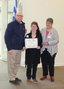 Jan Rettig holding her Extra Mile Award during the April 9, 2018 all-staff meeting. From left are division director Tim Slavin, Rettig and the division's National Register of Historic Places coordinator Madeline Dunn