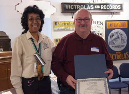 Andreas Lang holds his award during the rededication ceremony for the Johnson Victrola Museum. At left is museum site-supervisor Nena Todd