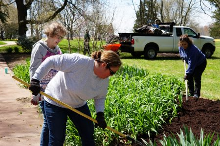 Delaware Department of State employees mulching a garden bed at the John Dickinson Plantation