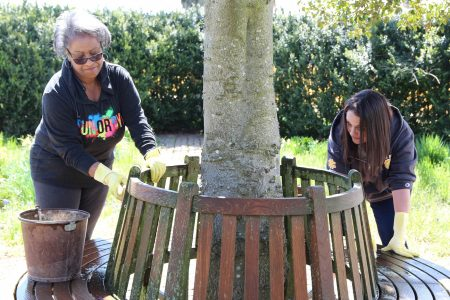 Delaware Department of State employees scrubbing a bench at the John Dickinson Plantation