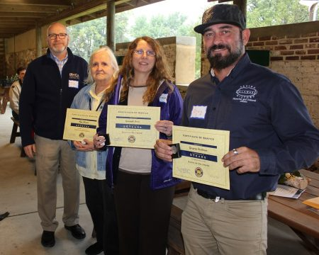 Division employees holding their staff-service awards. (From left) Division director Tim Slavin, Faye Stocum, Gwen Davis and Greg Buchman