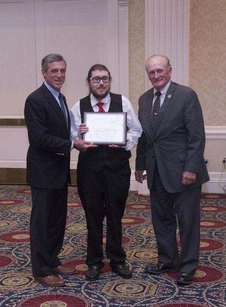 Jason Bakke receiving his award from Gov. John Carney. (From left) Carney, Bakke and state Rep. Dave Wilson