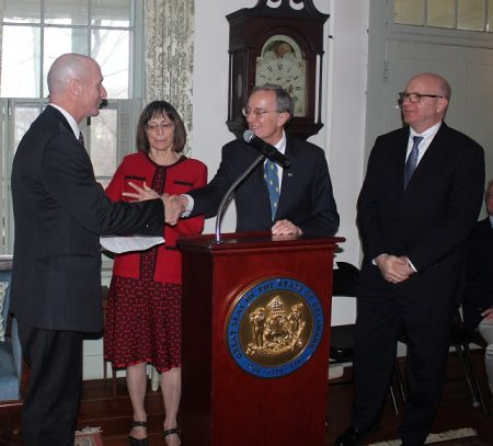 Delaware Secretary of State Jeff Bullock shakes hands with Richard R. Cooch at the Dec. 7, 2018 event celebrating the transfer of the Cooch property to the State of Delaware. (From left) Bullock, Anne Cooch Doran, Richard R. Cooch and Division of Historical and Cultural Affairs Director Tim Slavin