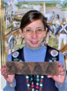 Beth Gott at the Zwaanendael Museum holding a Dutch cookie mold called a koekplank.