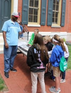 "Carlton Hall of the State Historic Preservation Office describing a ""shutter dog"" to a group of students."