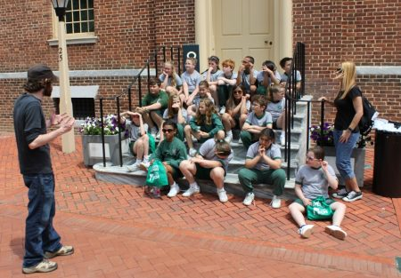 Museum staff member Chris Hall (left) addressing a group of students seated on The Old State House steps.