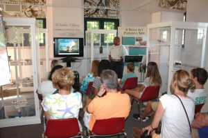 """Visitors listening to a lecture on DeBraak at the Zwaanendael Museum. Sections of the exhibit """"A Seaborne Citizenry: The DeBraak and Its Atlantic World"""" are on display in the room."""