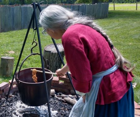 Photo of historic-site interpreter Jennifer Dunham demonstrating how fabric was dyed in the 18th century.