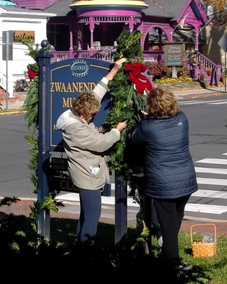 Photo of members of the Sussex Gardeners decorating the Zwaanendael Museum sign for the holidays in 2017.