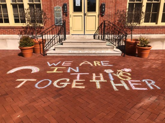 "Photo of the sidewalk in front of the division's main office in Dover with the words ""We are in this together"" written in chalk."