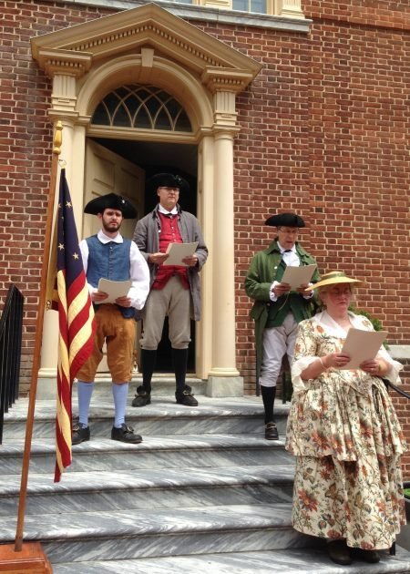 Photo of historical interpreters reciting the Declaration of Independence from the steps of The Old State House.