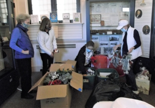 Photo of members of the Sussex Gardeners preparing to decorate the Zwaanendael Museum for the holidays.