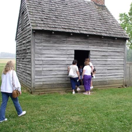 Photo of visitors exploring the John Dickinson Plantation's log'd dwelling