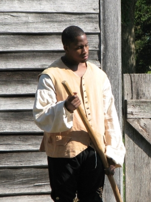 Photo of a volunteer interpreter portraying an enslaved laborer working at the John Dickinson Plantation.