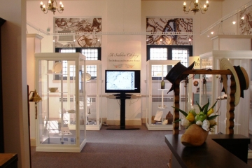 A wide view of the entrance to the DeBraak ship exhibit showing objects in several display cases