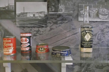 Food and drink containers in front of black and white photographs as part of the Delaware Railroads exhibit